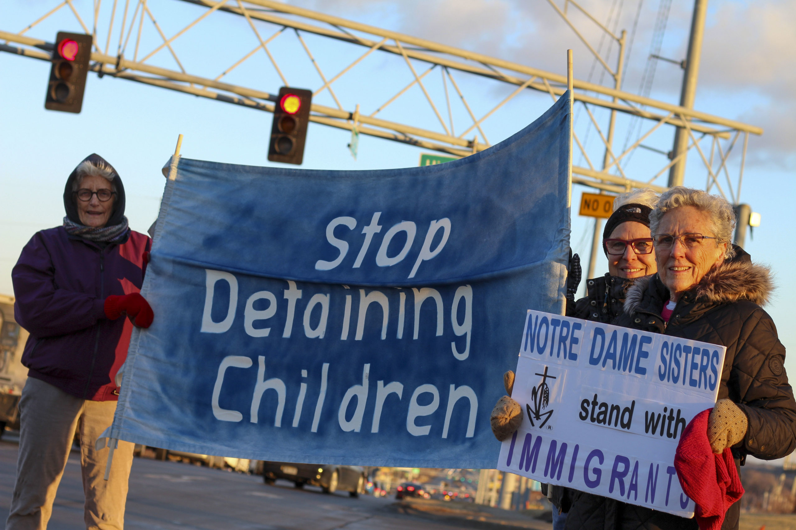 nds holding signs to stop detaining children