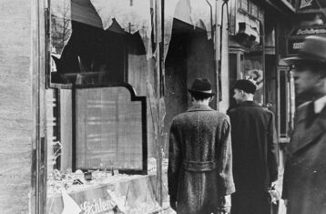 black and white photo of germans walking by jewish business destroyed