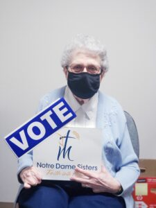 sister holding vote sign