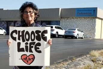 sister holding choose life sign