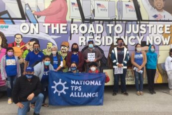 group in front of bus holding national tps alliance flag